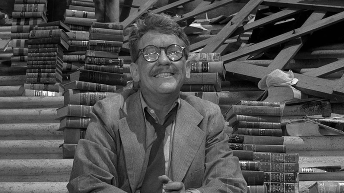 "Burgess Meredith sits outside a library, surrounded by books in the classic Twilight Zone episode ""Enough Time At Last."""