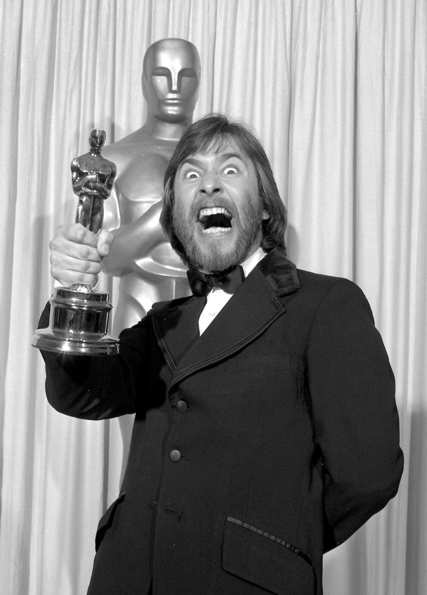 Rick Baker making a scary face as he excitedly holds up his first Oscar.