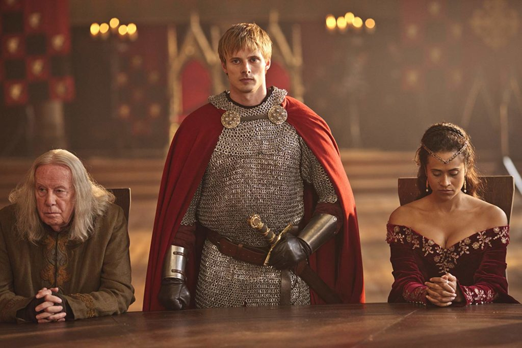 King Arthur stands at the round table with advisors Gaius and Queen Guinevere