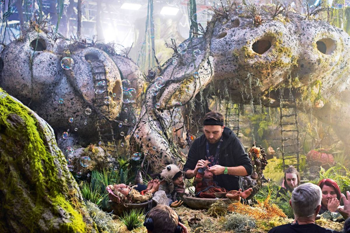 A behind the scenes look of someone on set of The Dark Crystal: Age Of Resistance making final fixes to a Podling puppet.