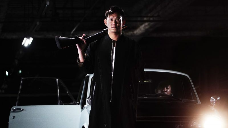 'One Arm' Wang arrives on the scene while holding a shotgun.