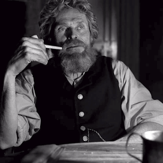 Willem Dafoe as Thomas Wade smokes a pipe in The Lighthouse.