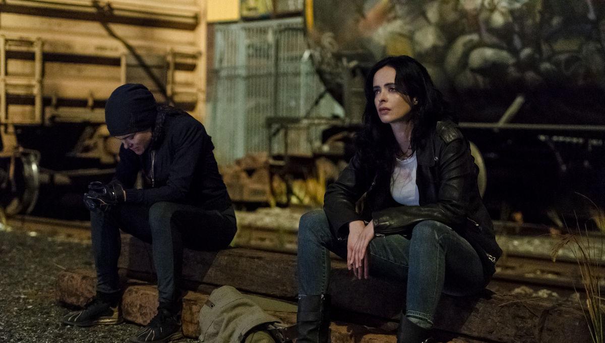Jessica Jones sitting next to someone in the series Marvel's Jessica Jones on Netflix.