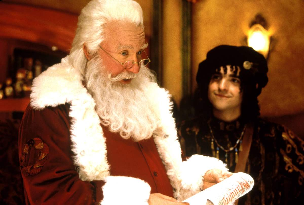 Santa is getting prepared for the holiday season by reading the naughty list as Bernard watches him.