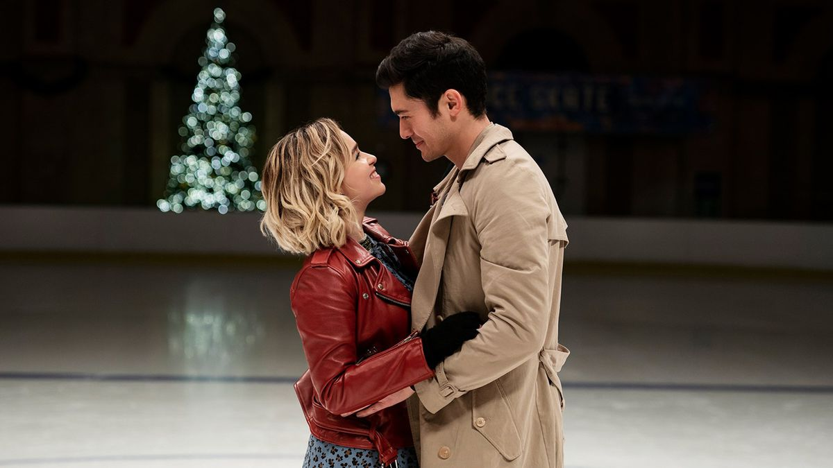 Kate and Tom are on an ice rink holding each other and smiling.