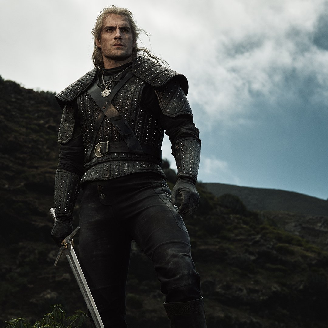 The witcher, Geralt of Rivia, stands valiantly on a mountain side with sword in hand.