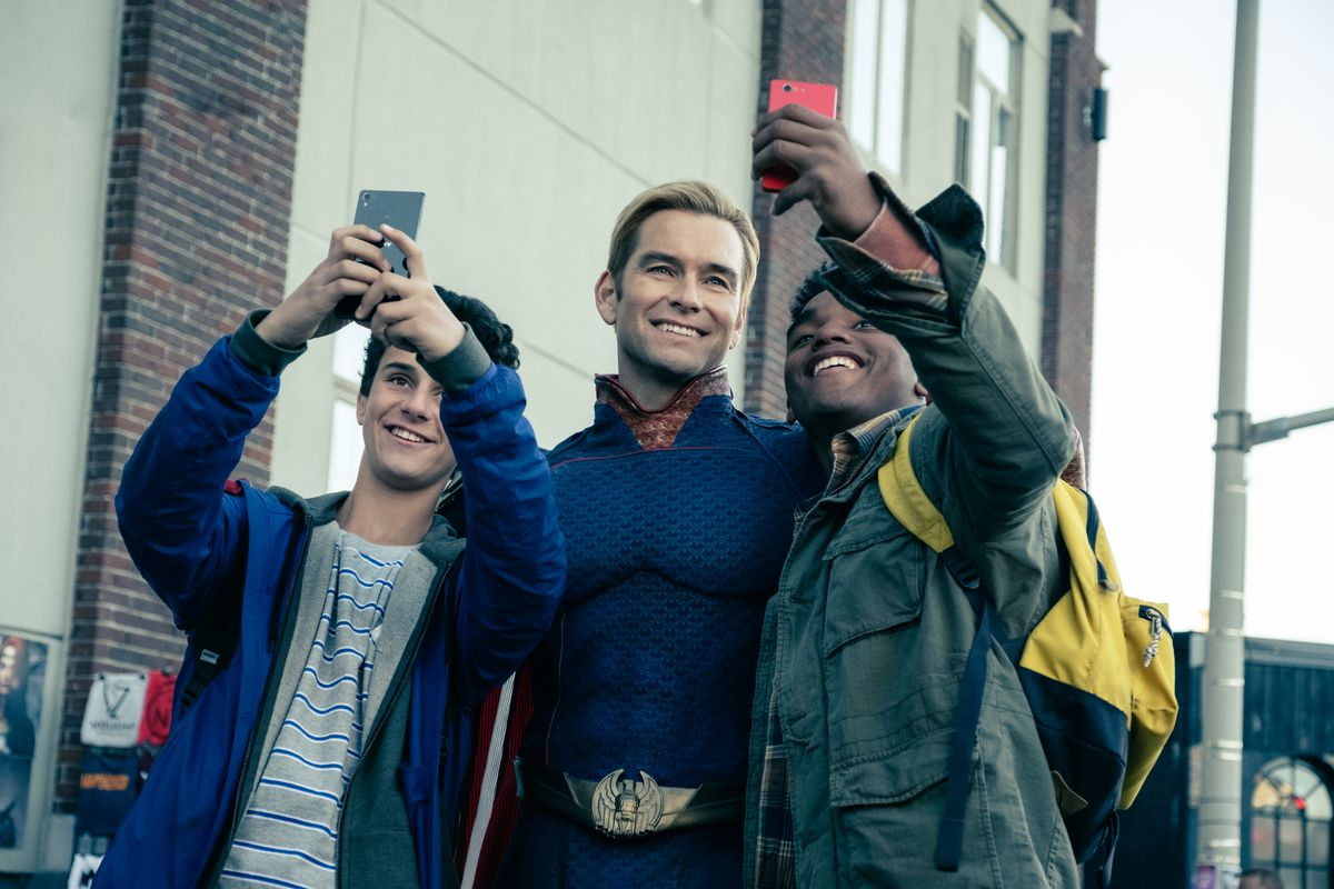 Two teenage boy fans take a selfie of themselves with the number one superhero, Homelander.