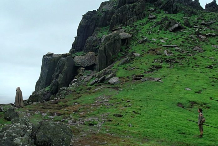 Rey reaches the top of the mountain on Ahch-To to find Luke.