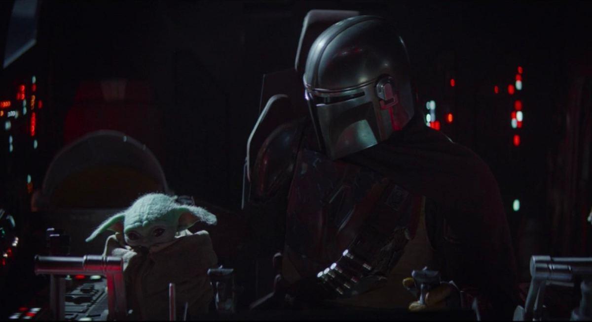 Mando looks down at Baby Yoda while piloting his ship.