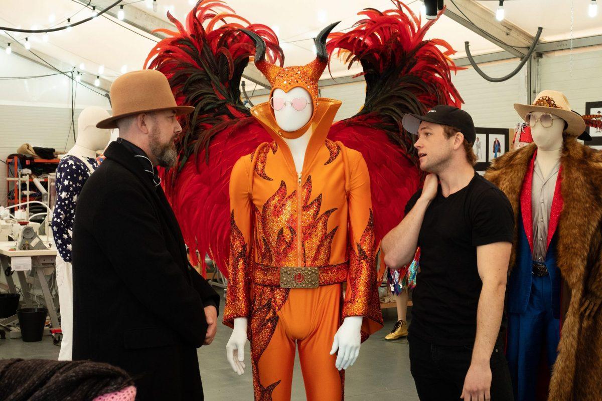 Julian Day, costume designer for Rocketman, shows the costumes to star Taron Egerton.