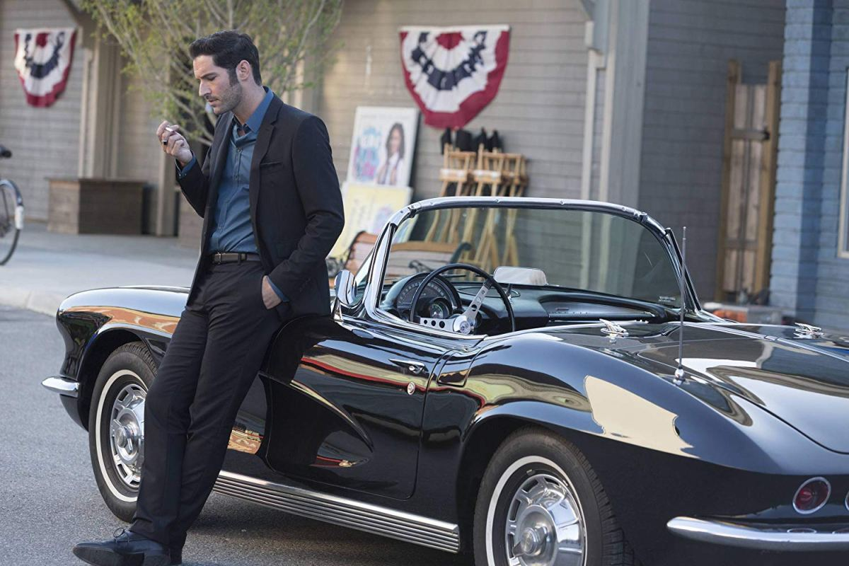 Lucifer Morningstar leans on a Corvette convertible.