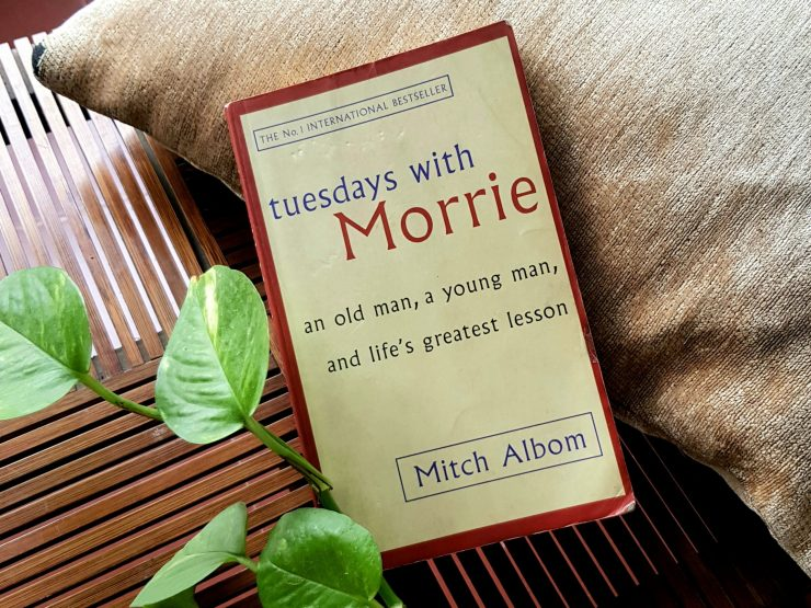 Books: Flat lay of Albom's book on a table next to a plant.