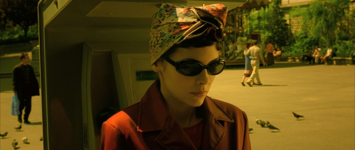 Amelie is in disguise, wearing a trench coat, headscarf, and large sunglasses, as she waits near a pay phone.