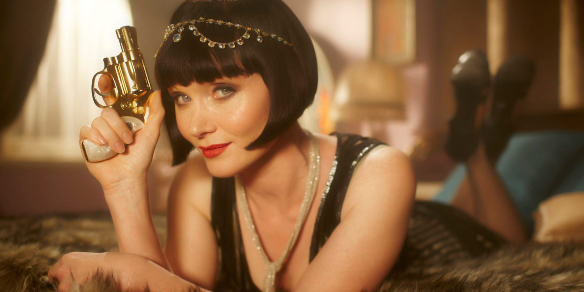 Phryne Fisher laying on a bed holding her pear handled pistol.