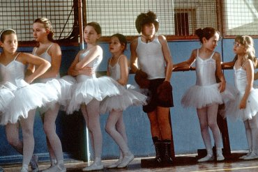 A child boxer and ballerinas in a line.