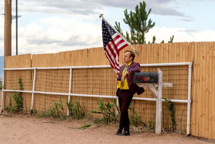 Saul Goodman leans on a client's mailbox under an American flag.