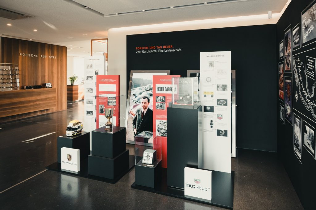 """The main parts of the exhibition at Porsche auf Sylt are based on this unique history. The exhibition initially leads through the historic """"Milestones"""" section, where the first Heuer Carrera chronographs dating back to 1964 and 1965 (Ref.2447SN, Ref.3147S and Ref.3647N) are located. In the large atrium at Porsche auf Sylt, visitors have a chance to see the Porsche 550 Spyder from 1954. This appears to be flanked by historic chronometric instruments from TAG Heuer, such as the electronic timepiece Heuer Startomat from 1968, a time measuring board with three Heuer stopwatches from 1970, which can be started successively thanks to a special lever mechanism, or the stopwatches Heuer Trackmate (Ref.593) and Heuer Trackmaster (Ref.8042) from 1978"""