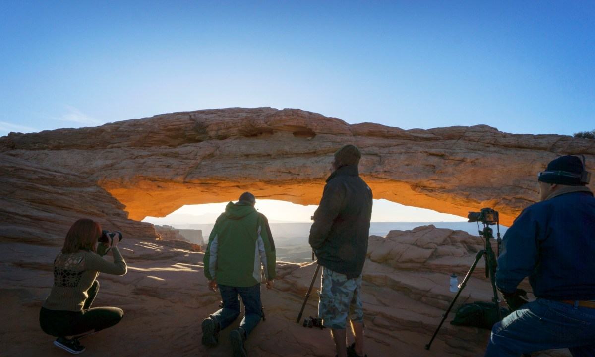 people standing near mesa arch waiting for the perfect portrait