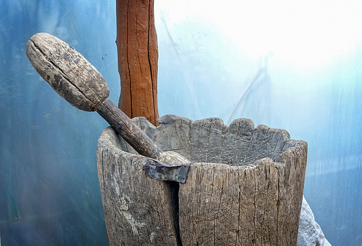 an old coffee grinder stick in an ancient bucket