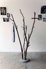 Porte-manteau en branches naturels plantés dans un socles en béton