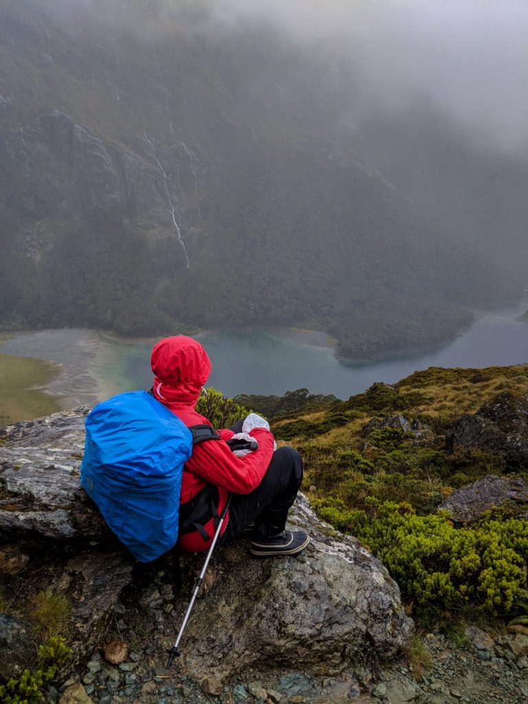 Soggy, Snowbound And Stoked // Routeburn Track (NZ), Rachel Dimond, Day 2 - Lake Mackenzie from the Hollyford face, waterproofs, rain cover, backpack, river, valley lookout, view