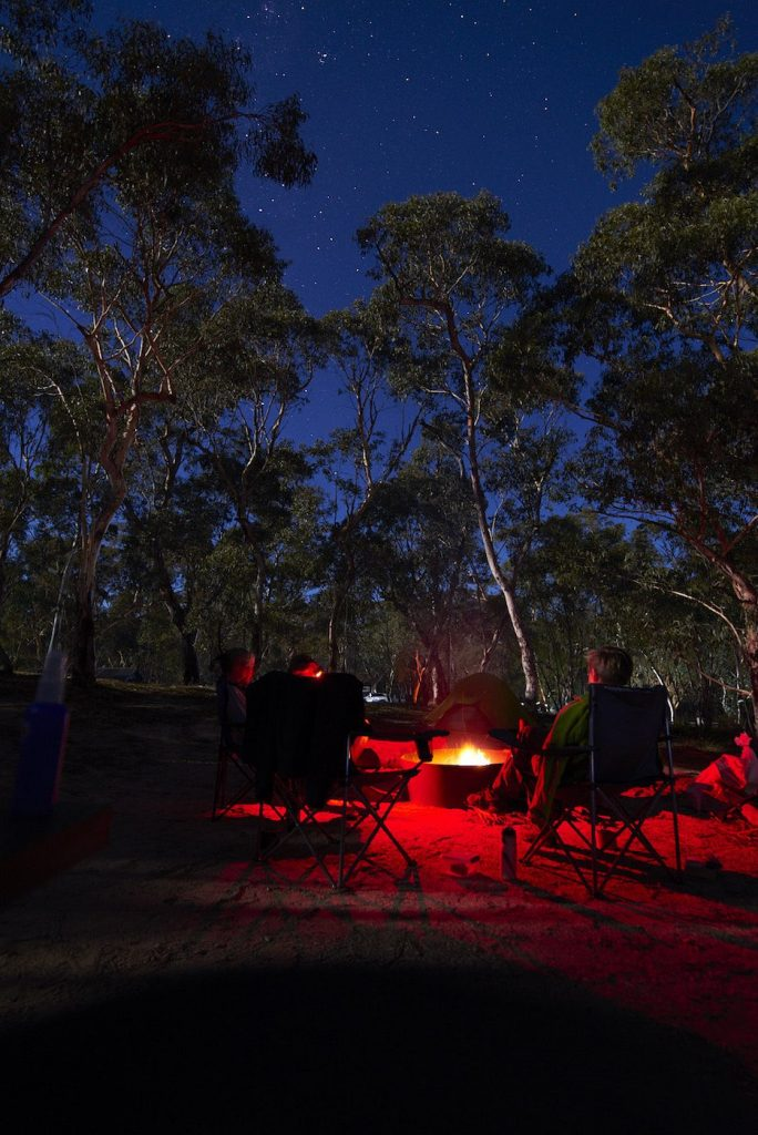 How To Make An Awesome Campfire Without Matches, Neil and Gabbi Massey, fire pit. flames, sitting round the fireside. group, evening, yarn