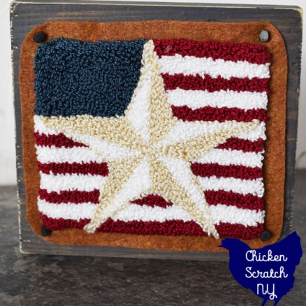 punch needle barn star mounted on felt and attached to a wooden block