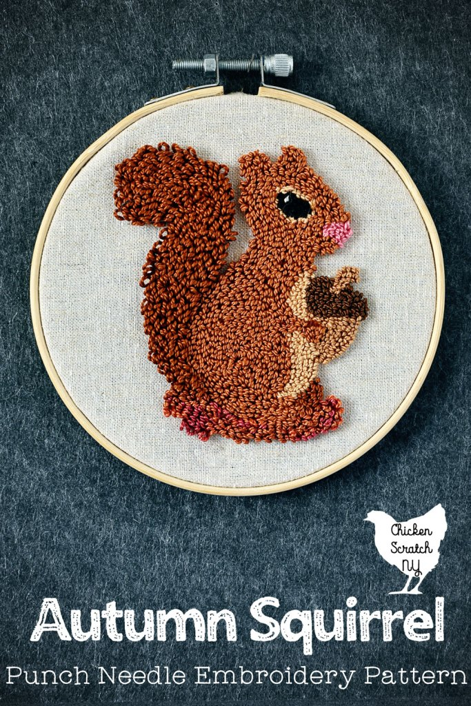 punch needle squirrel with a fluffy tail holding onto an acorn stretched in a plain wooden embroidery hoop