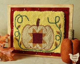 punch needle embroidery pumpkin with a burgundy and gold star surrounded by green vines with gold leaves