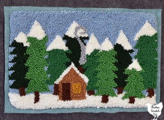 wintery scene punch needle embroidery pattern with rows of snow covered trees in multiple shades of green with a small cabin