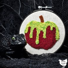 poison apple punch needle embroidery pattern on weavers cloth in black embroidery hoop with a black plastic frog