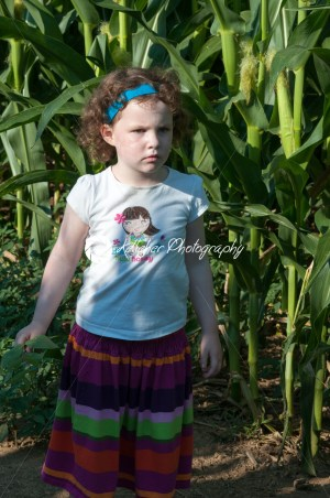 Girl in front of corn field green open space with mature trees on a sunny day with light clouds at Stroud Preserve - Kelleher Photography Store