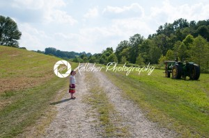 Girl on dirt pathway surrounded by green open space with mature trees on a sunny day with light clouds at Stroud Preserve - Kelleher Photography Store