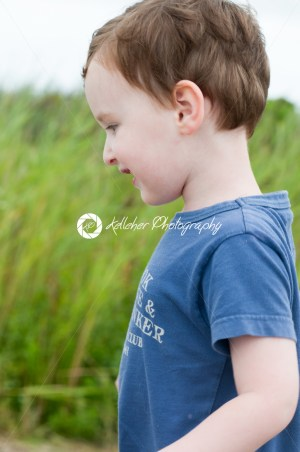 Profile of young boy walking outside along beach sand dunes with reeds - Kelleher Photography Store