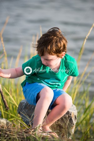 Young boy holding stick from among the reeds along the bay - Kelleher Photography Store