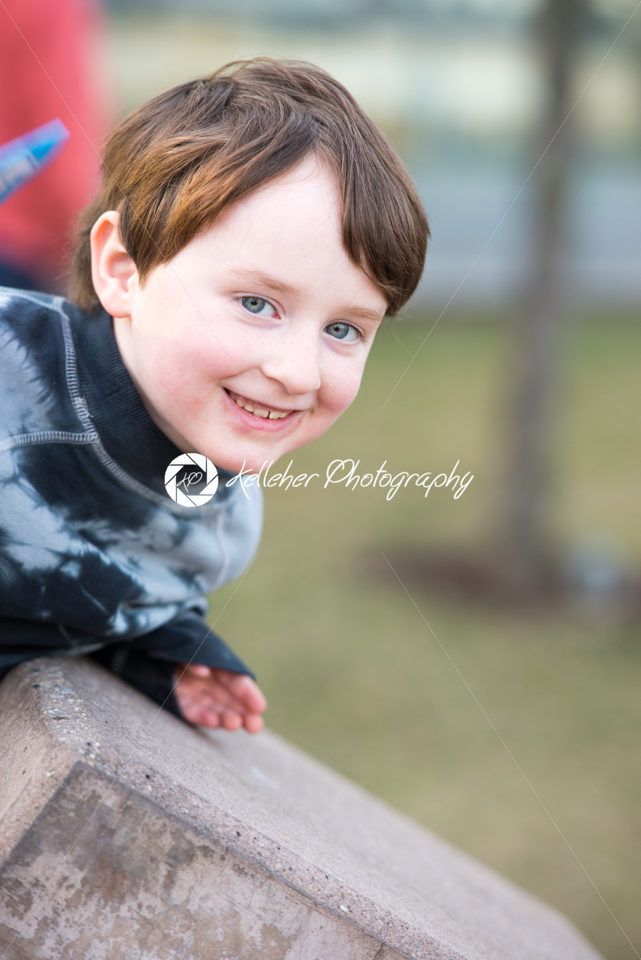 Young boy leaning over looking and smiling - Kelleher Photography Store