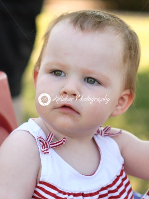 Young girl riding in red wagon having fun in the park for July Fourth - Kelleher Photography Store