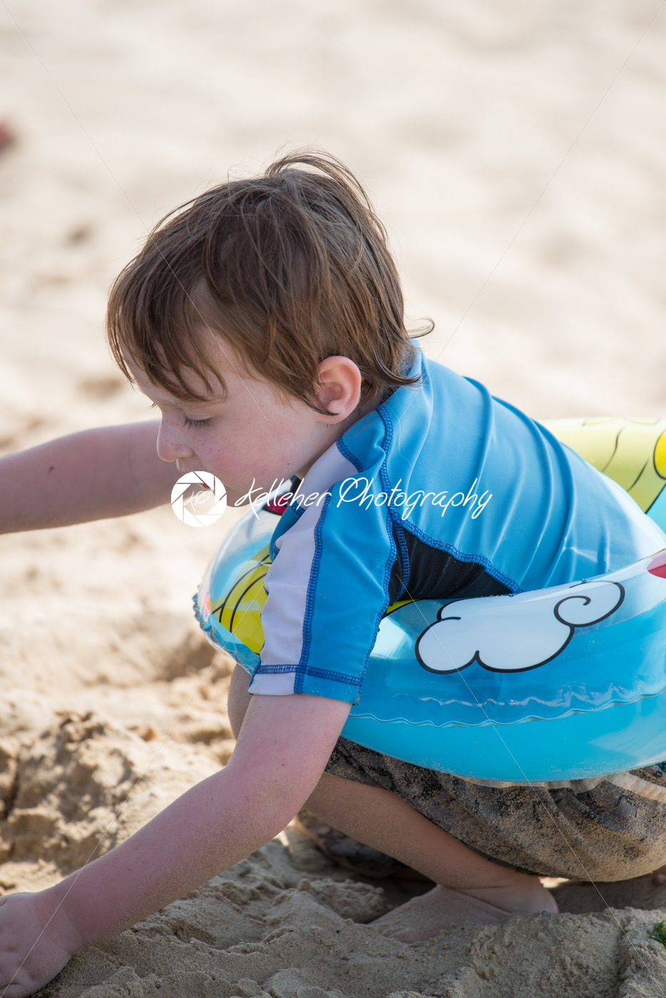 Young little boy playing with the sand and building sandcastle at the beach near the bay. - Kelleher Photography Store