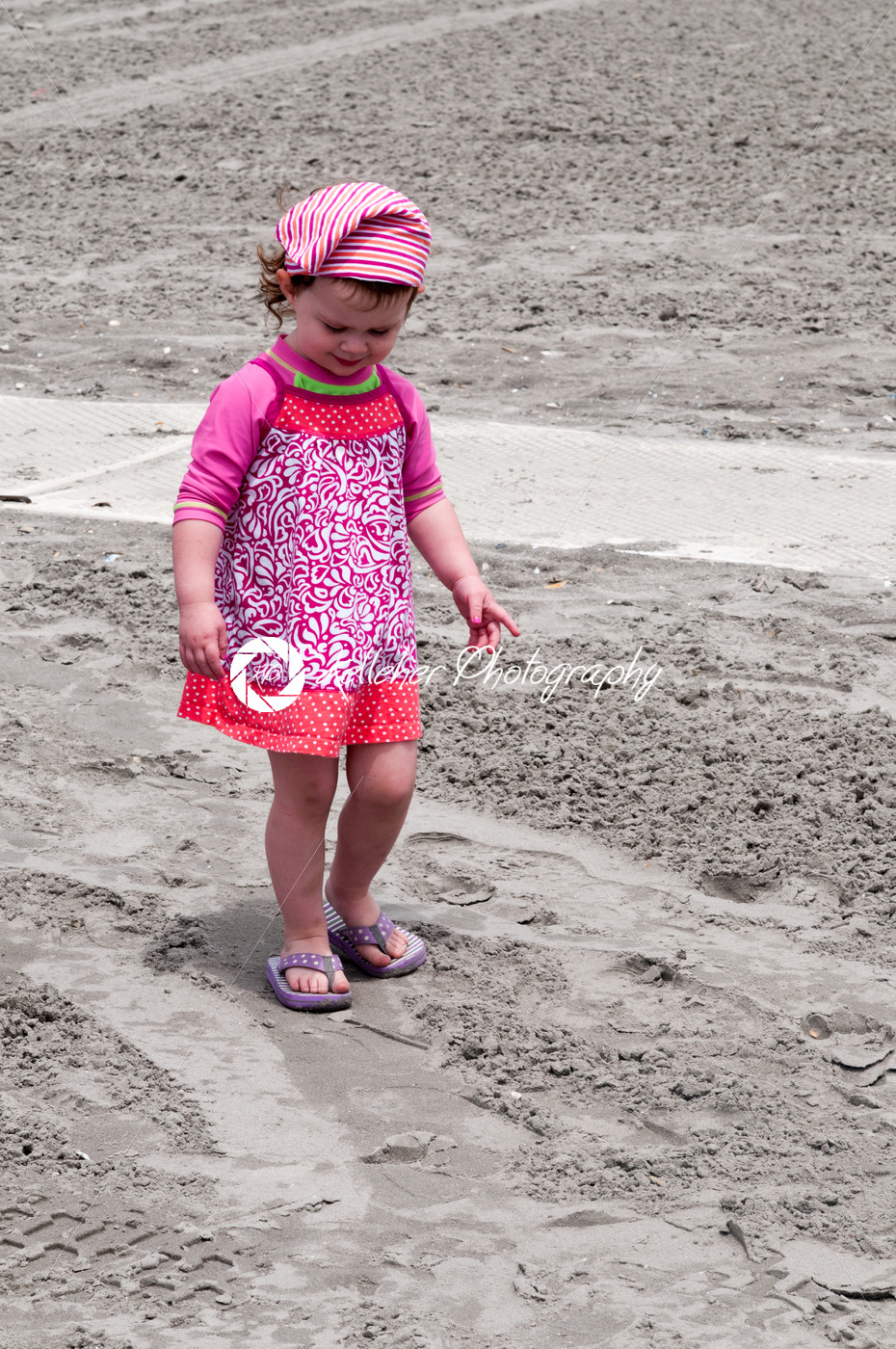 Young little girl playing with the sand and building sandcastle at the beach near the sea. - Kelleher Photography Store