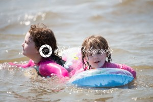 two young girls floating in inner tubes in a blissful state - Kelleher Photography Store