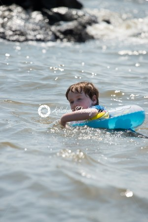 young boy floating in inner tubes in a blissful state - Kelleher Photography Store