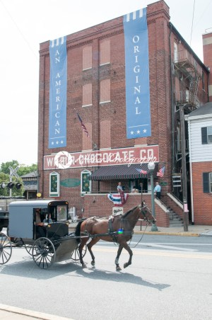 LITITZ, PA – AUGUST 30: Amish horse and buggy riding past the famed Wilbur Chocolate Company headquarters on Route 501 in Lititz on August 30, 2014 - Kelleher Photography Store