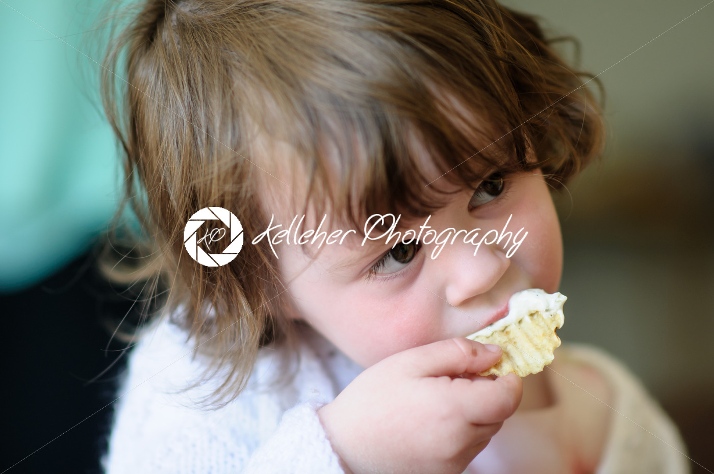 Portrait of a cute little girl inside eating potato chip with sour cream dip on it - Kelleher Photography Store