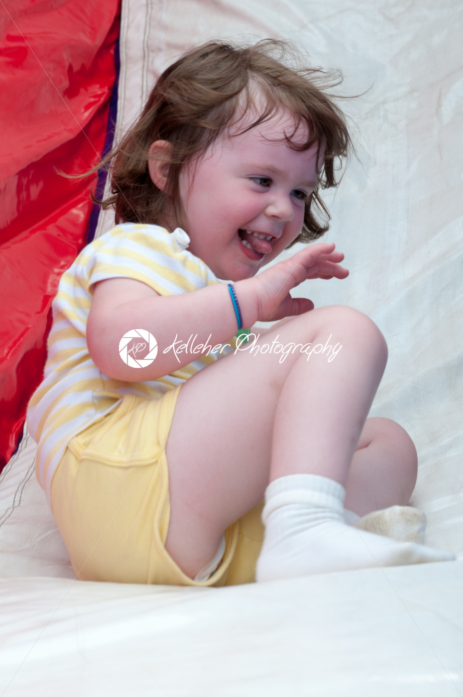 Young happy girl child riding inflatable slide outdoors on a warm summer day. - Kelleher Photography Store