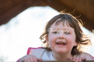 Young girl having fun outside at park on a playground swing set - Kelleher Photography Store