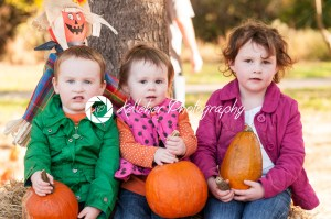 Young siblings outside holding a pumpkin with pumpkin fields in the background - Kelleher Photography Store