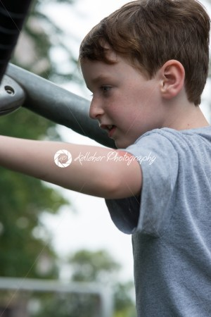Young boy having fun outside at park on a playground climbing set - Kelleher Photography Store