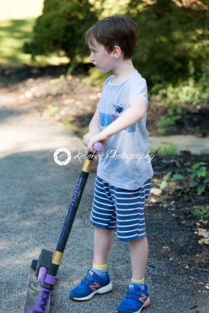Young litte boy outside riding his scooter in the driveway - Kelleher Photography Store