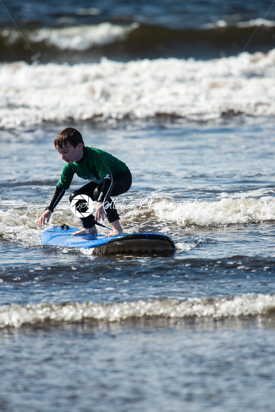 Young little boy on beach taking surfing lessons - Kelleher Photography Store