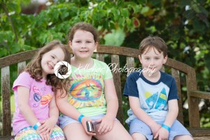 Three young siblings sitting on bench outdoors - Kelleher Photography Store